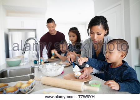 Family baking cupcakes glaçage et dans la cuisine Banque D'Images