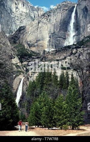 La plus haute chute d'eau en Amérique du Nord, les chutes de Yosemite est une attraction majeure dans la région de Yosemite National Park, qui a été créée en 1890 comme le premier parc national dans l'état de Californie, aux États-Unis. Situé dans les montagnes de la Sierra Nevada, Yosemite Falls gouttes 2 425 pieds (739 mètres) à partir du haut de la partie supérieure de l'automne (à droite) jusqu'à la base de la partie inférieure de l'automne (à gauche). Les visiteurs du parc à deux positions sur un sentier à la Lower Falls à échelle donner cette superbe vue panoramique à partir de la vallée de Yosemite. Le meilleur moment pour voir les chutes est à la fin du printemps, surtout en mai, lorsque le débit d'eau est habituellement à son apogée. Banque D'Images