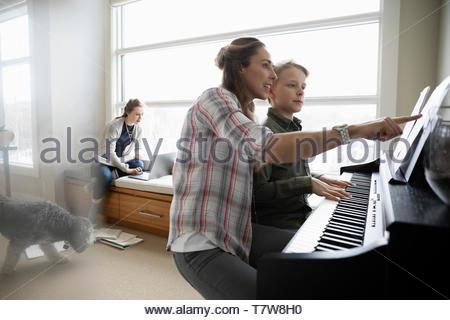Aider mère fils fille tout en pratiquant le piano n'en arrière-plan de devoirs Banque D'Images