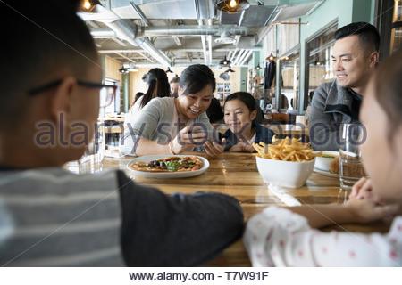 Famille avec smart phone à manger table restaurant Banque D'Images