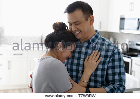 Affectionate couple hugging in kitchen Banque D'Images