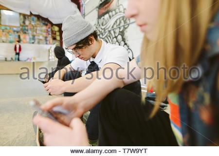 Des amis à l'aide de téléphones intelligents au skate parc d'intérieur Banque D'Images