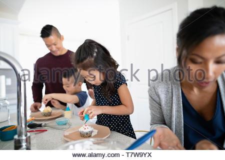 Family decorating cupcakes dans la cuisine Banque D'Images