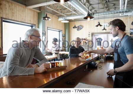 Barman mâle servant dégustation de bière à des clients en vols brewhouse Banque D'Images