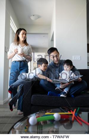 Livre de lecture en famille sur le sofa du salon Banque D'Images