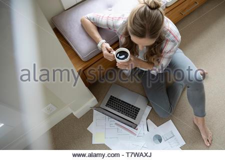 Vue de dessus femme travaillant à la maison, à l'aide d'ordinateur portable et de boire du café sur marbre Banque D'Images