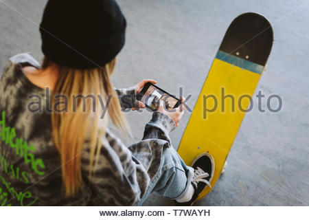 Teenage girl with skateboard regardant la vidéo sur téléphone intelligent Banque D'Images