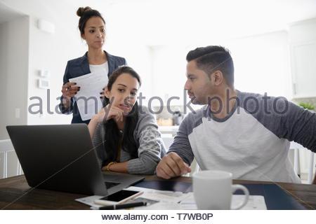 Conseiller financier rencontre avec couple at laptop en salle à manger Banque D'Images