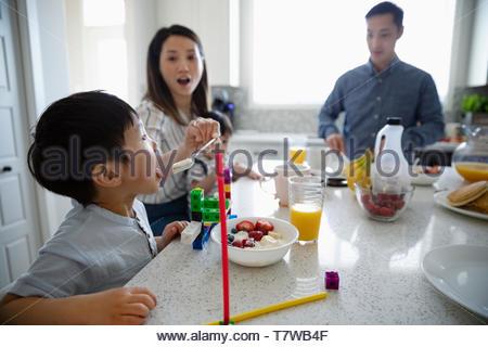 L'alimentation de la famille petit-déjeuner à l'île de cuisine Banque D'Images
