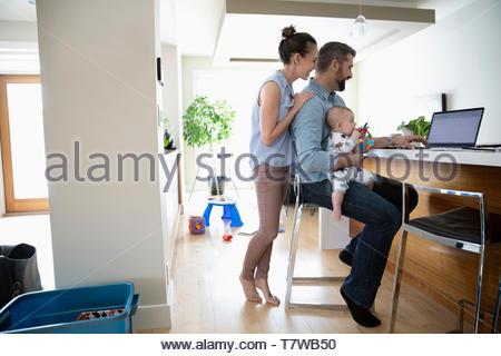 Les parents avec bébé using laptop in kitchen Banque D'Images