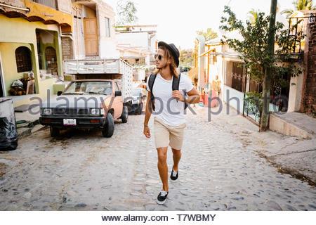 Jeune homme marche touristique sur rue pavée, Mexique Banque D'Images