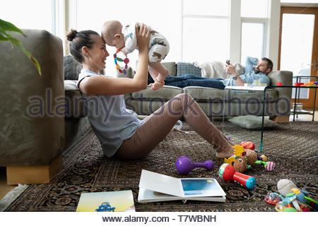 Heureuse mère jouant avec son bébé dans la salle de séjour Banque D'Images
