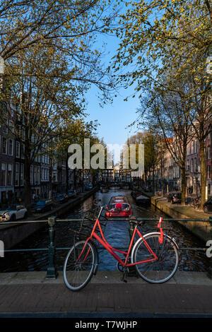 Parking vélo rouge sur le pont sur l'eau calme d'un canal avec un bateau donnant un aller-retour pour les touristes, Amsterdam, Pays-Bas
