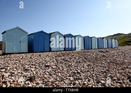 Charmouth Plage, Dorset, UK - Cabines de plage en bois sur une plage de galets à Charmouth avec ciel bleu en arrière-plan Banque D'Images