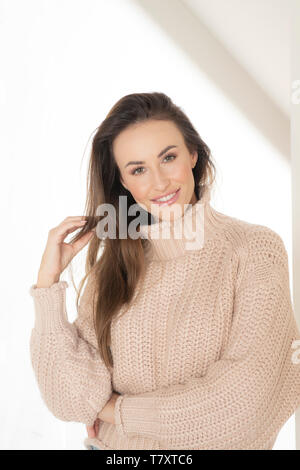 Smiling woman in sweater beige Banque D'Images