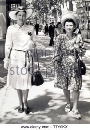 Habillé à la mode femme deux adultes promenade sur une journée ensoleillée France 1945 Banque D'Images
