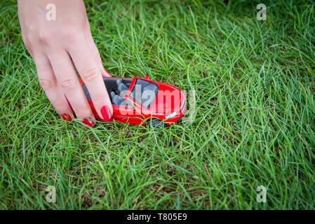 La main féminine est titulaire d'un jouet voiture rouge sur l'herbe verte Banque D'Images