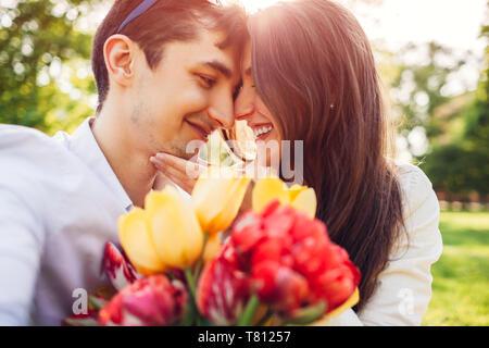 Happy young couple in love hugging avec bouquet de fleurs du printemps à l'extérieur. Homme doué sa petite amie avec des tulipes