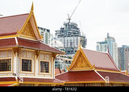 Temple thaï en face de construction urbaine. Représentant de la religion et de la civilisation urbaine, le bâtiment et la construction sont, à Bangkok, à fond. Banque D'Images
