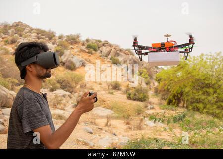 Jeune homme essayant de contrôler par le contrôleur de drones en voyant la réalité virtuelle au spectateur. Banque D'Images