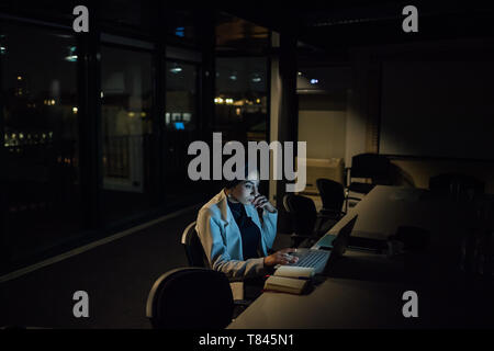 Young businesswoman in office at night typing on laptop