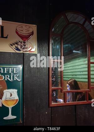 Manchester, Royaume-Uni - 19 Février 2019: une fille regarde l'écran de son téléphone portable assis derrière une vitre dans un pub à Manchester Banque D'Images