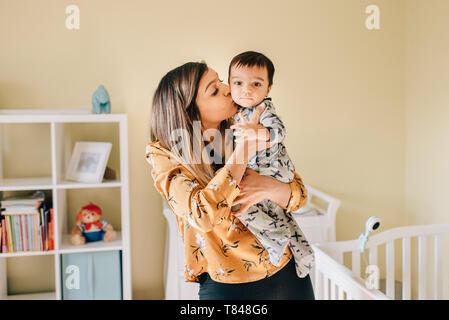 Mère embrassant bébé fils en pépinière, portrait Banque D'Images