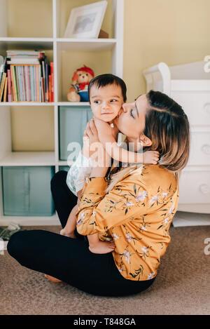 Assis sur le sol de pépinière Mère embrassant bébé fils Banque D'Images