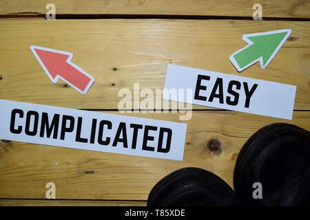 Compliqué ou facile en face des panneaux de direction avec des bottes sur le sol en bois vintage. Concepts d'affaires et d'éducation Banque D'Images