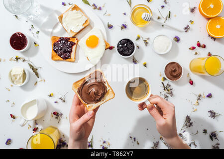 Portrait de femme tenant toast avec crème au chocolat et une tasse de café express près de petit-déjeuner sur white Banque D'Images
