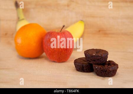 Un petit tas de brownies à côté d'une pomme, banane et orange faire différents choix de desserts Banque D'Images