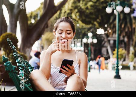 Heureux femme latine à l'aide de téléphone mobile en Amérique latine, fille mexicaine au Mexique