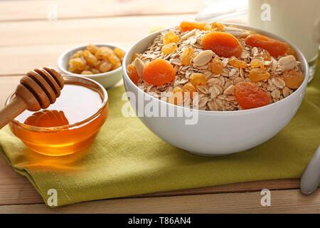 Flocons d'avoine avec bol, les fruits séchés et les noix sur la table en bois Banque D'Images