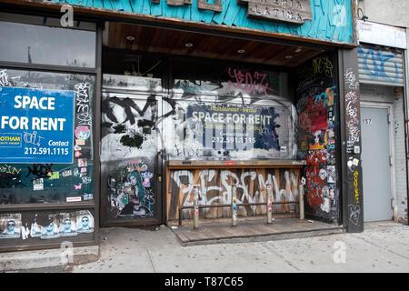 Un magasin vacant à louer sur Houston Street à Manhattan couvert de graffitis, autocollants et étiquettes. Lower East Side, New York City. Banque D'Images