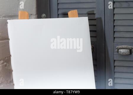 Un chevalet avec une toile blanche et est prête à travailler contre un mur en brique blanche, l'arrière-plan ou d'un concept sur l'art. Banque D'Images