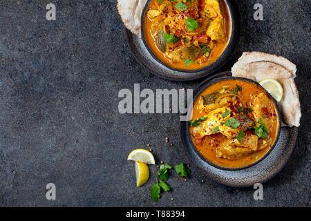 Nourriture indienne. KERALA traditionnel curry de poisson avec du pain naan, plaque de fond noir, gris
