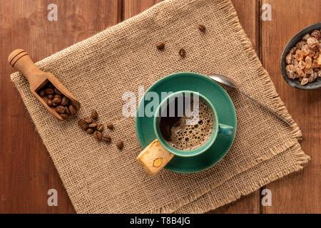 Une tasse de café noir avec un cookie, de café torréfié et caramel brun sucre, tourné par le haut sur un fond de bois rustique foncé Banque D'Images