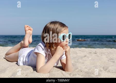 Funny little girl (7 ans) en lunettes se trouve sur la plage. Focus sélectif.