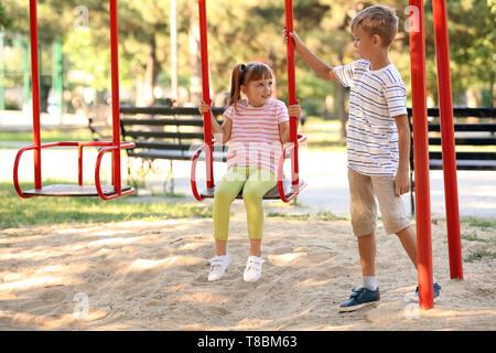 Cute little boy poussant sa sœur sur des balançoires en plein air Banque D'Images