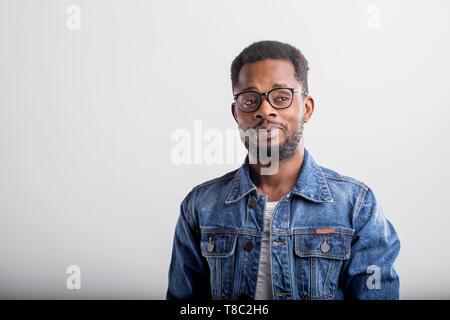 Portrait de bon à certain African American male avec petite barbe portant des T-shirt casual veste en jean et posant contre fond studio gris
