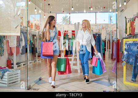 Smiling attractive blonde and brunette sortant de vêtements boutique en centre commercial. Deux amis avec des sacs d'achats se regarder, parler et rire. Concept de bon shopping. Banque D'Images