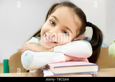 Portrait de joli, drôle lycéenne avec des nattes en classe. Élève assis à 24, s'appuyant avec les mains sur les livres, en souriant. Photo de l'enfant, posant. Banque D'Images