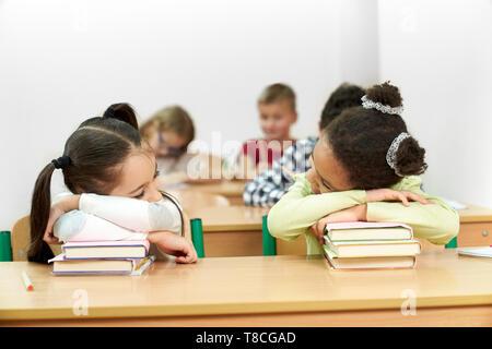 Jeune, jolie écolières, assis en classe à 24 et s'appuyant sur pile de livres. Camarade de dormir sur des livres. Des écoliers, des élèves qui étudient en classe. Banque D'Images