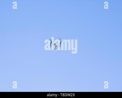 Drone en opération sur le ciel bleu clair Banque D'Images