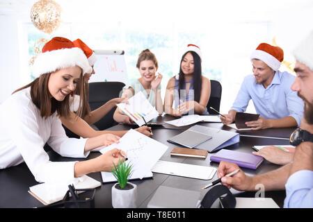 Les jeunes de Santa hats working in office Banque D'Images
