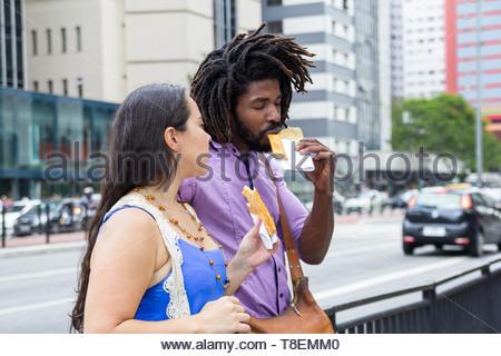 Couple multiethnique dans les rues la nourriture brésilienne appelée Pastel - recette asiatique. Banque D'Images