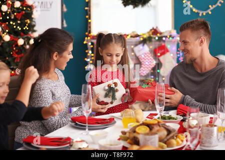 Petite fille cadeaux offerts par ses parents durant le dîner de Noël Banque D'Images