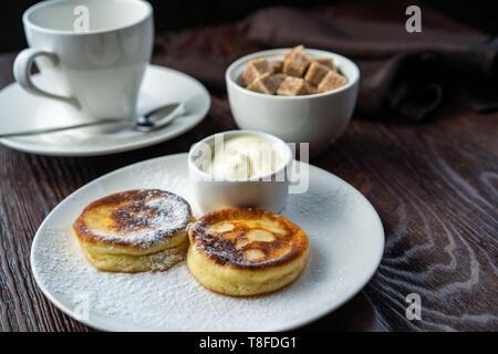 Les gâteaux sur une plaque blanche. À côté de la crème glacée est une tasse de crème sure et d'une cuillère. La crème glacée sont décorées avec une feuille de menthe fraîche Banque D'Images