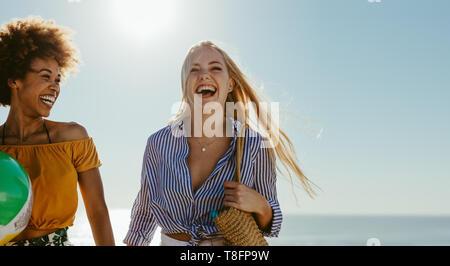 Best Friends smiling outdoors sur une journée ensoleillée. Deux jeunes femmes à marcher ensemble à la plage. Banque D'Images