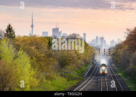 Un train s'approche en direction de l'aller à Toronto Danforth's East End près de coucher du soleil. Banque D'Images